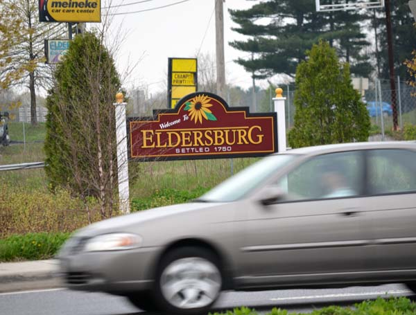A car zooms past the Welcome to Eldersburg sign.